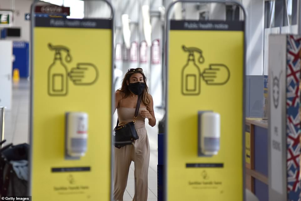 A passenger wearing a face mask arrives to to board Ryanair flight FR2190 to Malaga at London Southend Airport in Essex on Wednesday